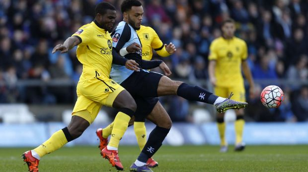 Wycombe Wanderers' Aaron Holloway and Aston Villa's Jores Okore battle for the ball.