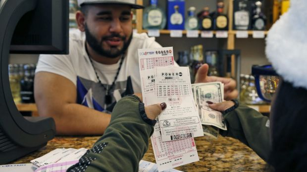 Samir Akhter, the owner of Penn Branch Liquor, sells Powerball tickets in Washington.