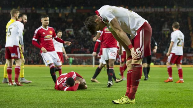 Reaction: Sheffield United's Dean Hammond after bringing down Manchester United's Memphis Depay for a penalty.