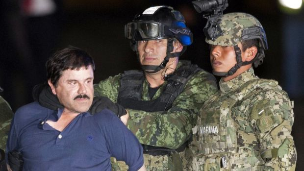 """Joaquin """"El Chapo"""" Guzman is escorted to a helicopter by Mexican soldiers and marines in Mexico City."""