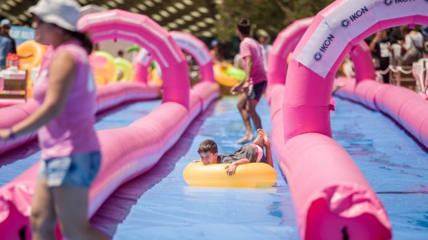 Locals and travellers escape Melbourne's summer at Federation Square's temporary waterslide.