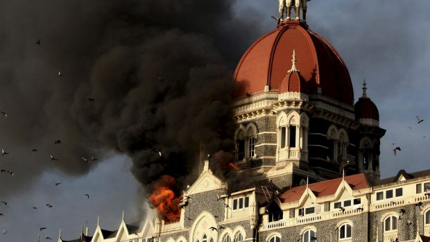 Under attack: Flames and smoke gush out of the Taj Mahal Hotel in Mumbai following the terror attacks in November 2008.