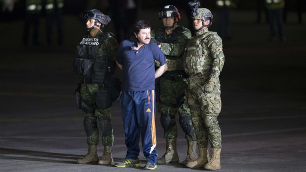 "Joaquin ""El Chapo"" Guzman is made to face the press as he is escorted to a helicopter in handcuffs by Mexican soldiers ..."