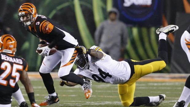 Duck and run: AJ McCarron is pulled down by Lawrence Timmons.