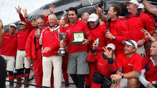 The captain of supermaxi Wild Oats XI Mark Richards (centre with trophy), celebrates with owner Bob Oatley and the ...