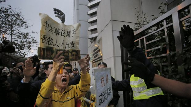 A protester shouts slogans outside the China Liaison Office in Hong Kong during a protest against the disappearance of ...