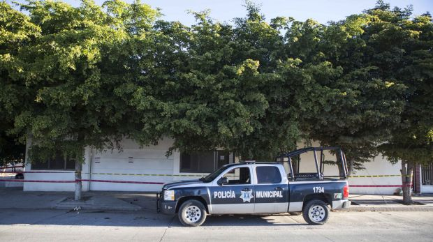 A police truck sits parked outside the house where marines engaged in a gun battle during the search for Mexican drug ...