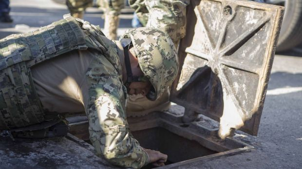 A Mexican marine inspects a manhole where high-powered weapons were found to be abandoned, in the neighbourhood where ...
