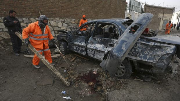 Afghanistan's municipality employees, in orange, clean up the site of a suicide attack claimed by the Taliban at Le ...