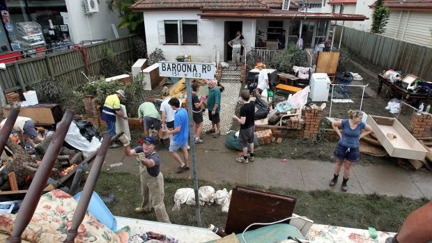Teams of volunteers descend on flood-affected suburbs to clean up.