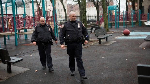 Police officers on Sunday cross Osborn Playground in the Brownsville section of Brooklyn, where an 18-year-old woman was ...