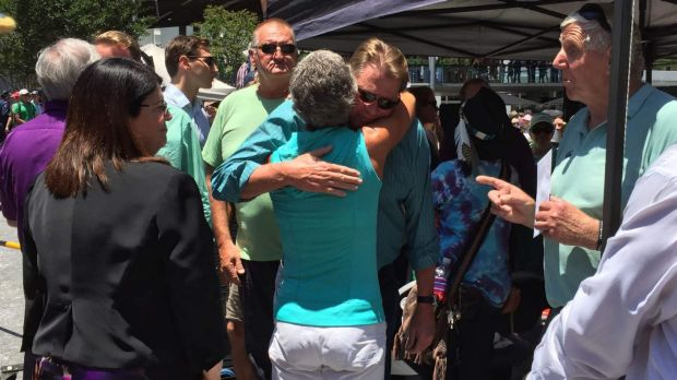 Well-wishers greet Cole Miller's father Steve at the a memorial.