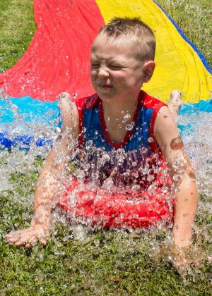 Six-year-old Callan Dunstan enjoying the waterslide at a family party in Gordon.