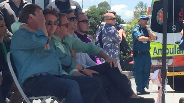 Cole Miller's brother Mitch, seated beside their other brother Billy, puts his arm around dad Steve.