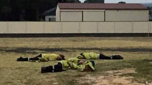 Exhausted firefighters kip on the lawn outside Harvey fire station.