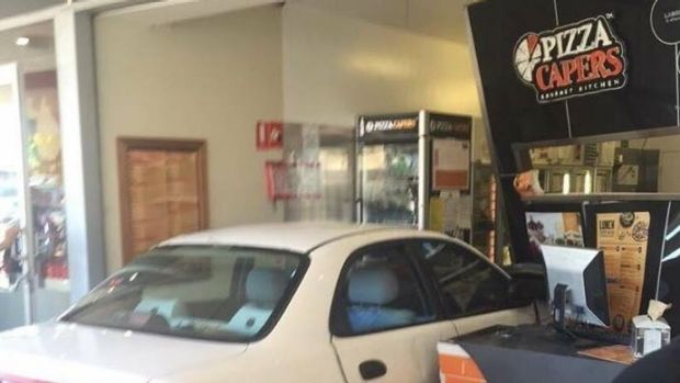A car crashed through the front window of the Pizza Capers store at Strathpine.