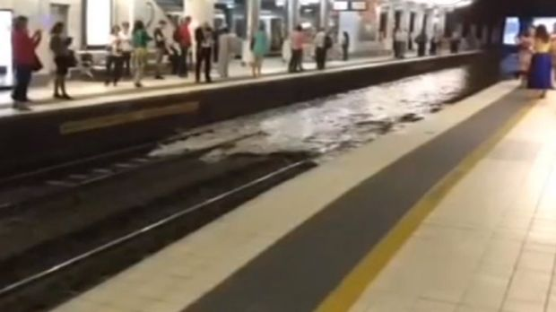 Shocked commuters watch rising floodwater cover the tracks at Fortitude Valley Station.