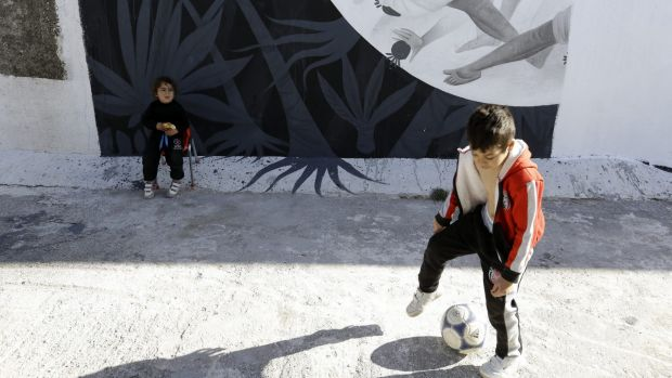 Children play at the Hellenikon shelter, a former Olympic  hockey venue, in southern Athens. A tightening of border ...