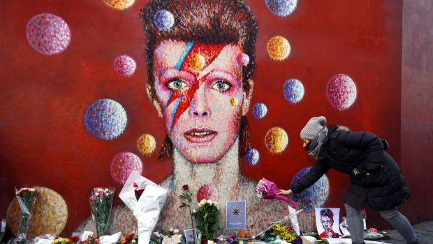 A woman leaves flowers beneath a mural of David Bowie in Brixton.
