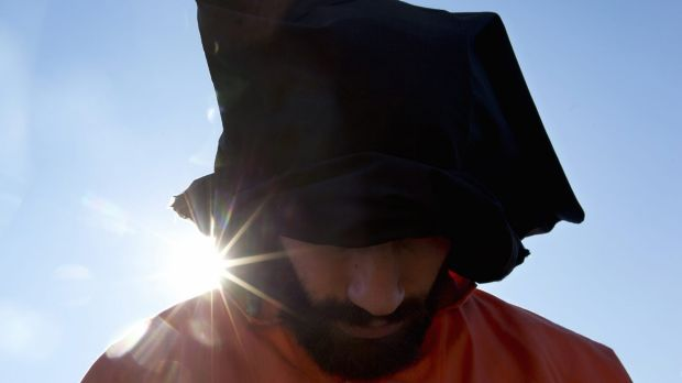 A protester wearing an orange jumpsuit depicting a Guantanamo Bay detainee, participates in a rally outside the White ...