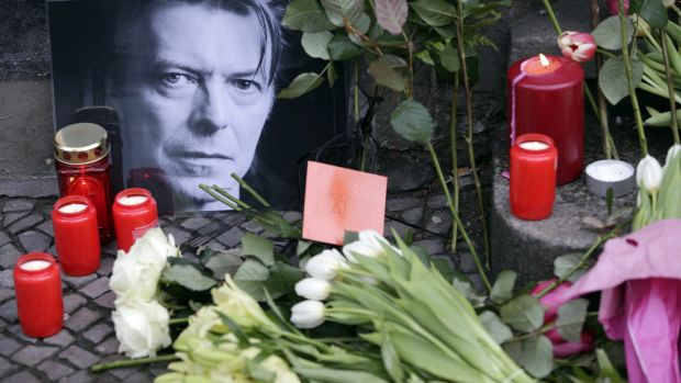 Flowers and a portrait are placed in front of the apartment building where David Bowie once lived in Berlin, Germany,