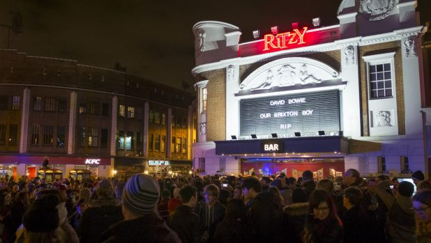 Members of the public gather outside the Ritzy Cinema in Brixton to pay tribute to David Bowie on Monday.