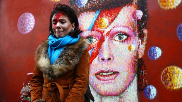 David Bowie fan Rosie Lowery placed flowers at his mural in Brixton, London, after the singer's death was announced on ...
