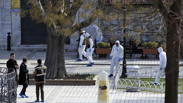 Turkish forensic police officers search for evidence at the site of the suicide bombing, in the historic Sultanahmet ...