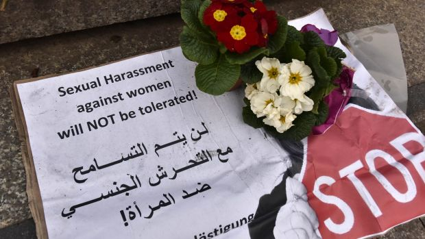 """A banner with flowers is placed on the steps to the Cologne cathedral says in English and Arabic """"sexual harassment ..."""