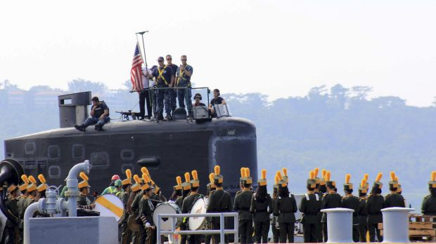A local marching band welcomes the arrival of sailors aboard the USS Topeka as it prepares to be docked off Subic port ...