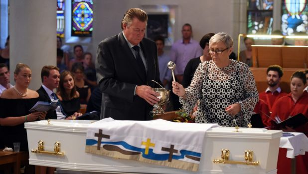 Steven and Mary-Leigh Miller sprinkle holy water on the coffin of their son, 18 year-old one-punch victim Cole Miller.