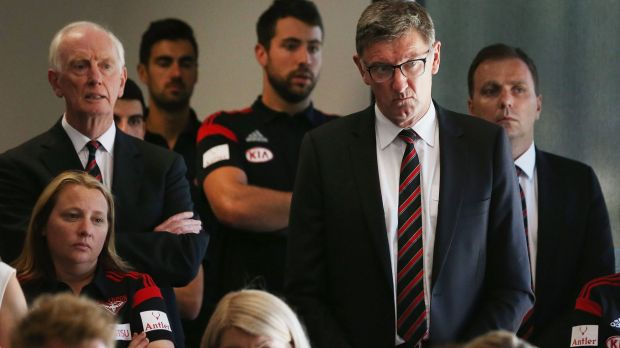 Essendon legend Simon Madden (second right) listens during a press conference at the club on Tuesday.