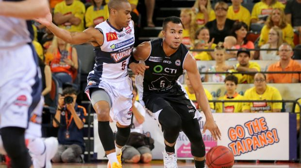 Melbourne United guard Stephen Holt holds off the advances of Markel Starks of the Cairns Taipans.