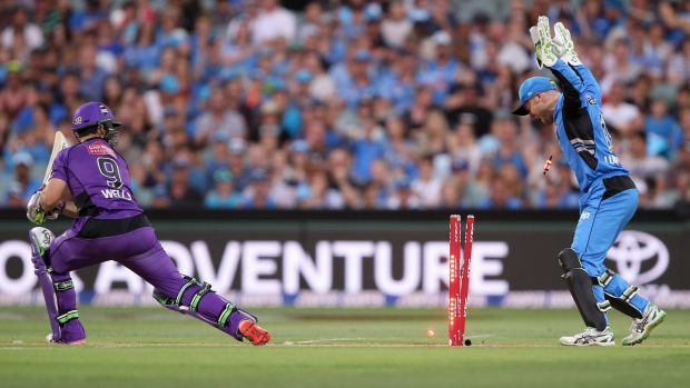 Jonathan Wells of the Hobart Hurricanes looks back at his shattered stumps as wicketkeeper Tim Ludeman rejoices.