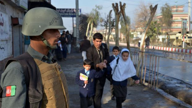 An Afghan member of the security forces stands guard as a man helps school children run from the site of clashes near ...
