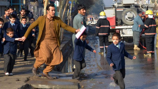 An Afghan teacher, in brown, helps school children run from the site of clashes near the Pakistan consulate in Jalalabad.