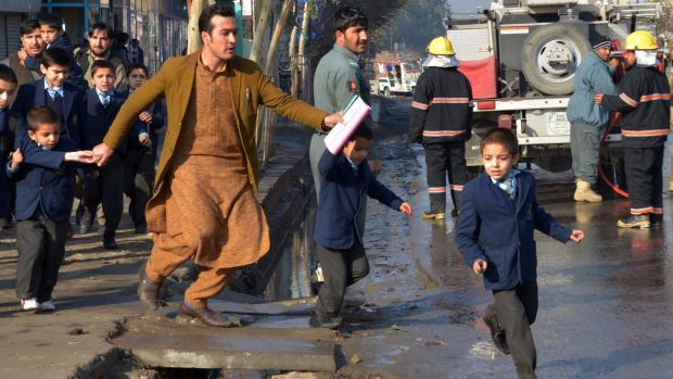 An Afghan teacher, in brown, helps school children run from the site of clashes near the Pakistan consulate in ...