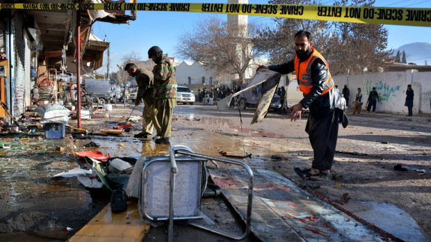 Pakistani police and rescue workers examine the site of suicide bombing that killed at least 15 in Quetta, Pakistan on ...