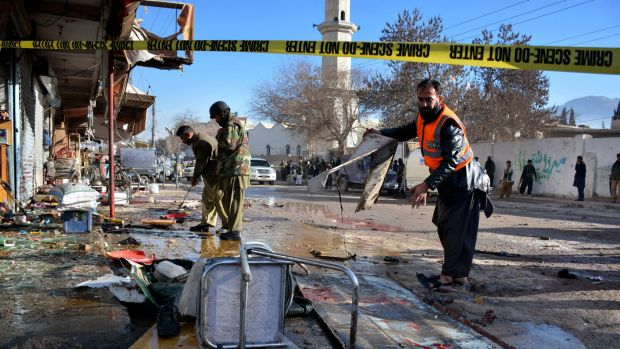 Pakistani police and rescue workers examine the site of suicide bombing that killed at least 15 in Quetta, Pakistan, ...