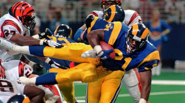 Lawrence Phillips leaps over a mound of players as he scores a touchdown for the Rams against the Cincinnati Bengals in 1996.