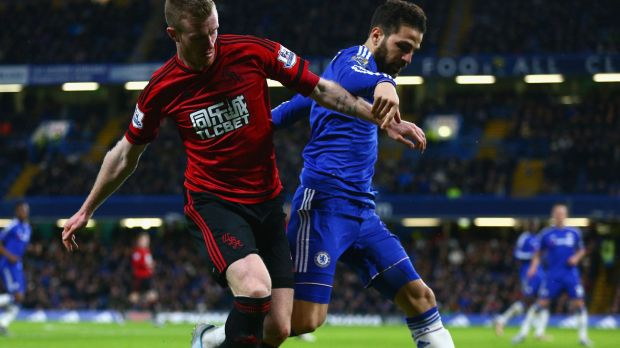 Cesc Fabregas of Chelsea and Chris Brunt of West Bromwich Albion compete for the ball.