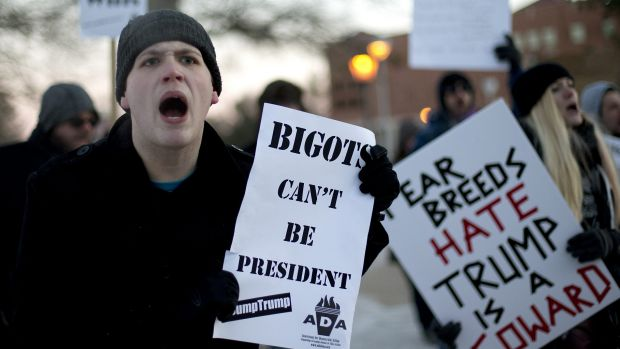 Logun Buckley, left, a senior at the University of Northern Iowa, protests against Republican presidential candidate ...