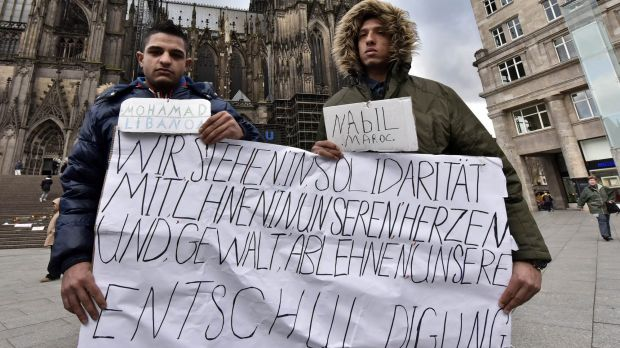 Mohamad of Lebanon, left, and Nabil of Morocco hold a banner in front of the Cologne cathedral to apologise for other ...