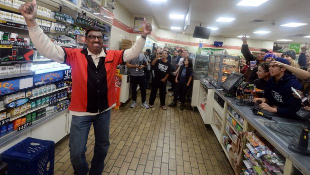 7-Eleven store clerk M Faroqui celebrates after learning the store sold a winning Powerball ticket.