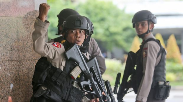 A police officer gives a hand signal to a squad mate as they search a building near the site of an explosion in Jakarta.