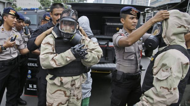 Members of the police bomb squad don protective gear prior to examining the site where an explosion went off in Jakarta ...