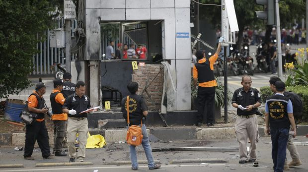 Police officers examine a police post where an explosion went off.