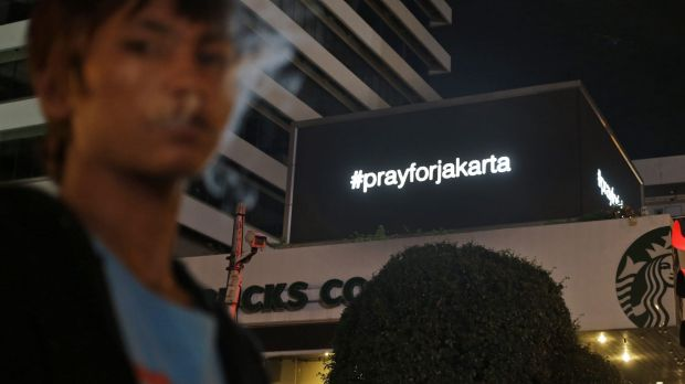 "An electronic screen above the Starbucks cafe where the attack took place displays the message ""#prayforjakarta""."