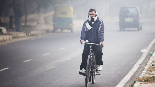 A cyclist travels along a road shrouded in smog in New Delhi, India.