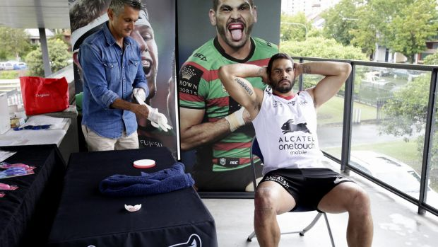 This won't hurt a bit: A Colgate official helps Greg Inglis with his mouthguard fitting at Redfern Oval on Friday.